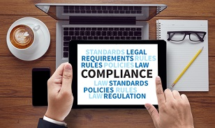 "businessman's hands holding a tablet displaying words like ""compliance,"" ""legal,"" ""rules"" and ""regulation."""