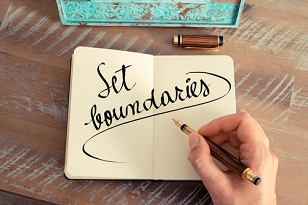 "Person's hand writing ""Set boundaries"" in a notebook with a fountain pen"