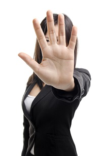 "Businesswoman holding up her hand in a strong ""stop"" gesture"