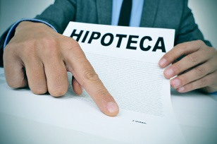 young caucasian man wearing a grey suit sitting at his office desk showing a document with the word hipoteca, mortgage loan contract in spanish, and where the signer must sign