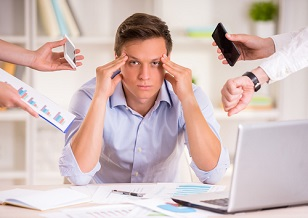 Stressed manager in his office being asked to do too many tasks at once