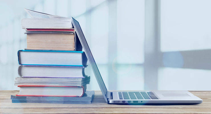 Laptop open with a stack of books piled up behind it. CUES Elite Access courses are available at a discount to CUES Unlimited and Unlimited Plus members.