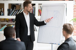 Businessman presenting diagram drawn on a large notebook to colleagues