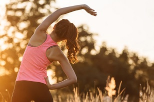 young woman warming up outdoors by stretching