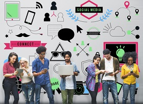 Group of Generation Z members using mobile devices, standing in front of a wall of illustrations depicting social media, trends and technology