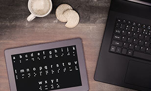 Braille on a tablet next to a computer and a cup of coffee