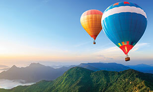 colorful hot air balloons soaring over mountains