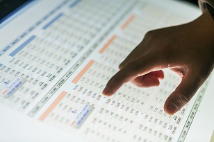 Hand pointing to data in a report on a screen