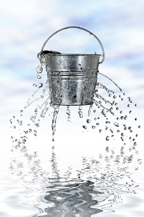 Water streaming out of a bucket full of holes