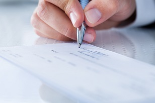 Close-up photo of a hand filling out a paper check
