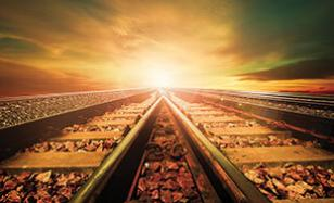 train tracks converging in front of a sunset sky